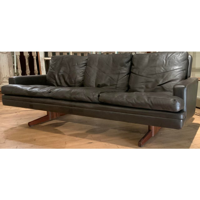 A 1960s three-seat sofa in dark brown leather and rosewood by Fredrik Kayser made by Vatne Mobler. Beautiful design and...