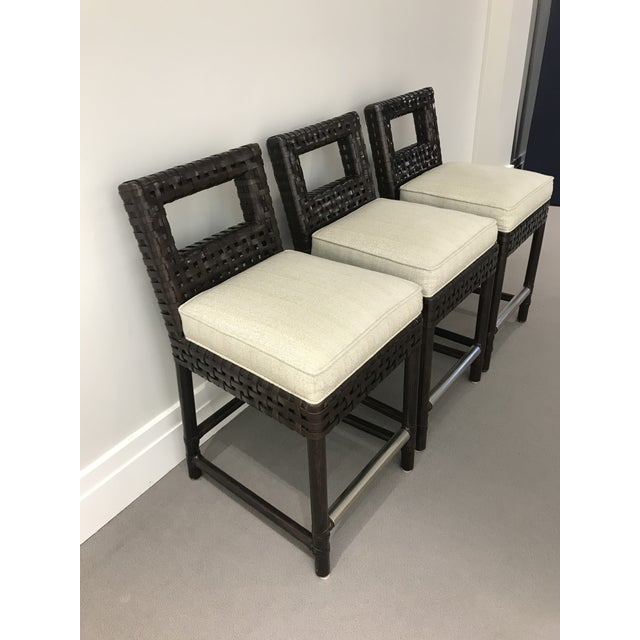 Set of 3 McGuire leather banded counter stools. These feature neutral, multi-colored linen upholstery and a dark chocolate...