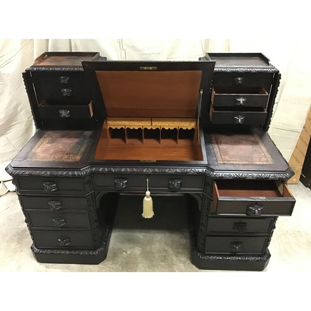 A Victorian carved Dickens desk with green man handles and a sloping writing surface. The upper left and right sides of...
