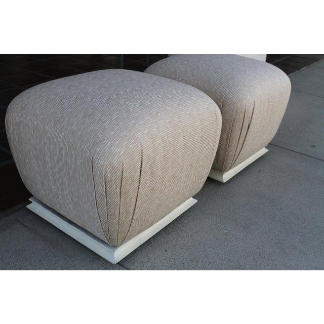 "Pair of ottomans we upholstered with painted bases. Ottomans measure: 20"" wide, 20"" deep and 18.5"" high."