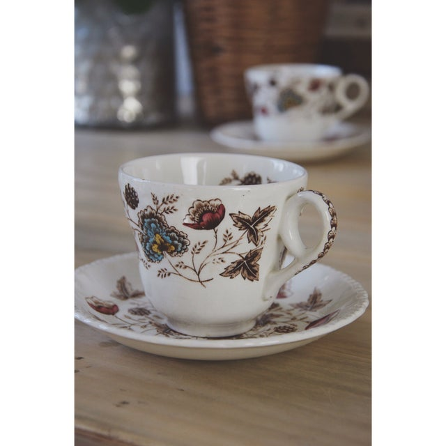An elegant pair of floral teacups and saucers. The motif is textile inspired with shades of brown, blue, and pink. This...