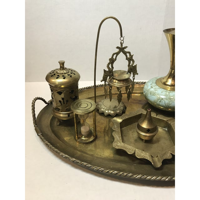 A multi-faceted set of vintage brass trinkets and decor objects on an Indian brass tray. Included are an hourglass,...