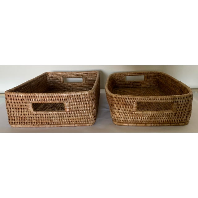Set of 2 contemporary brown rattan woven storage baskets. Baskets vary slightly in shape.
