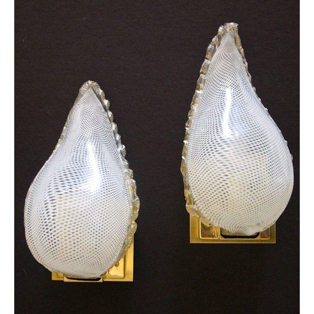 About Pair of clear and white latticino Murano glass wall sconces with gold inclusions in leaf shape form. Each sconce...
