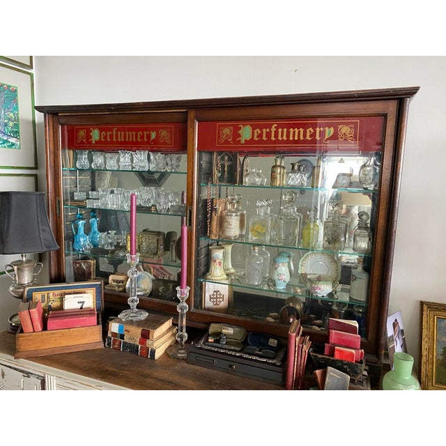 "Counter top perfume display cabinet with ""Prefumery' across the top of each sliding glass door. Doors with brass pulls...."