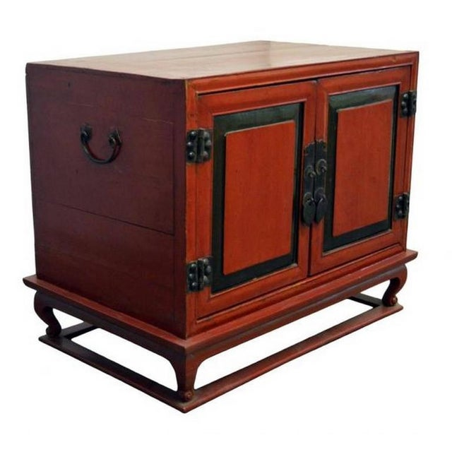 A mid-19th century Chinese bedside cabinet with red lacquered wood and brass hardware. This cabinet is made of a...