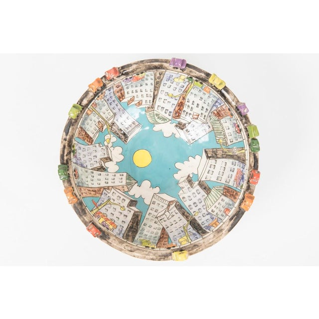 Imaginative ceramic bowl decorated with colorful urban landscape subjects by Canadian potter Misha Ferguson.