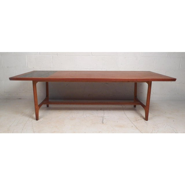 This large coffee table boasts a sturdy construction with a firm stretcher between the tapered legs. The table has a sleek...