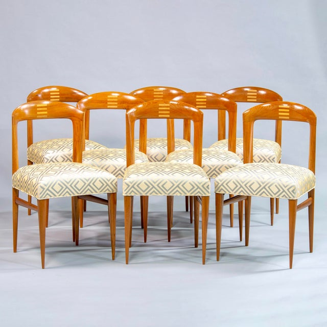 Circa 1940 set of eight polished Art Deco beech chairs. Open backs with curved tops feature inlaid design of stacked bars...