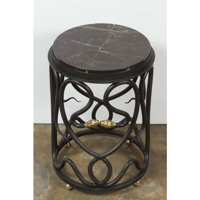 Paul Marra snake table. Steel table in bronze patina with brass snake heads and brass ball feet. Polished marble top is...