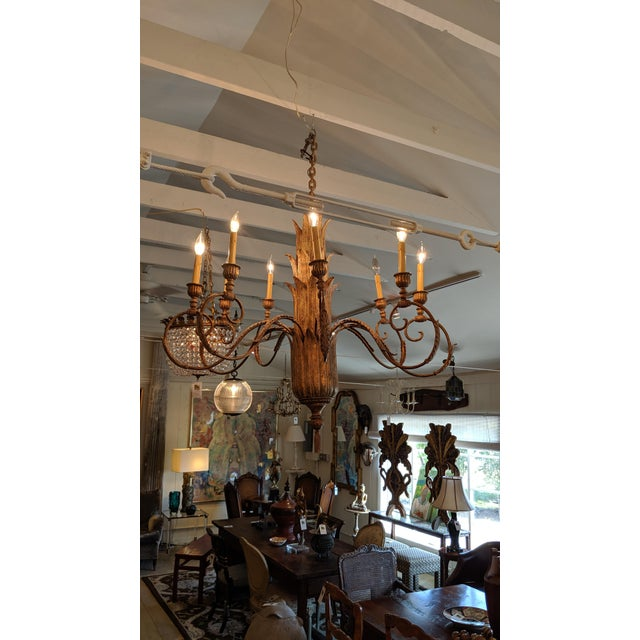 A very large impressive chandelier having a gilded finish over composite and copper having 9 curlicue elegant arms and a...
