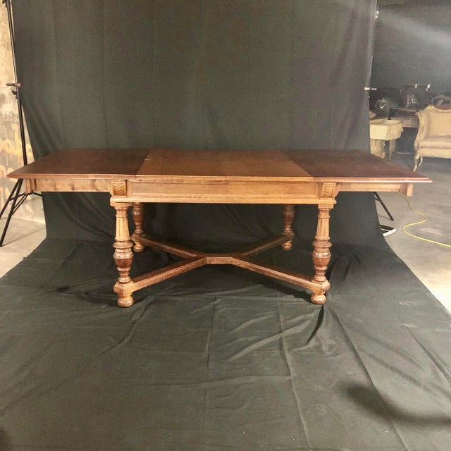 A versatile Art Deco or Arts and Crafts oak dining table having inset draw leaf that, once the sides are pulled apart,...