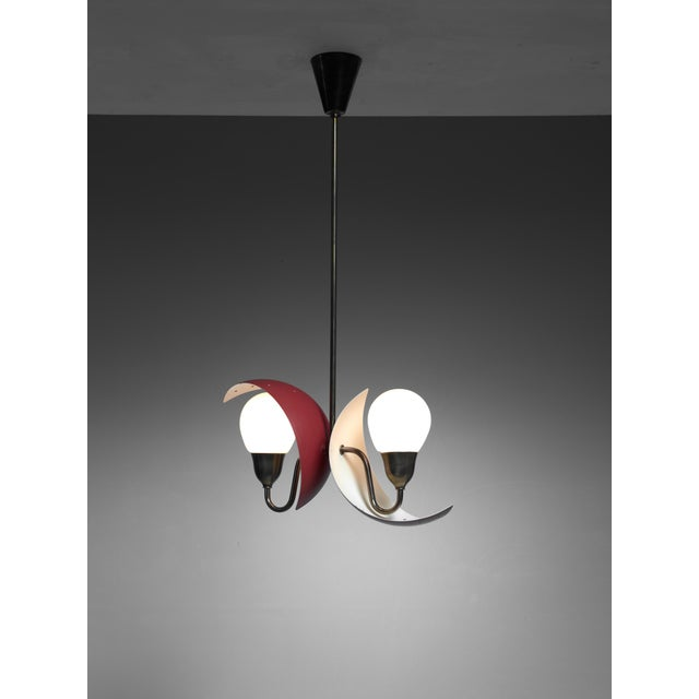 A Bent Karlby attributed pendant lamp for Fog & Mørup, Denmark. The lamp has two crescent shaped dark red metal shades...