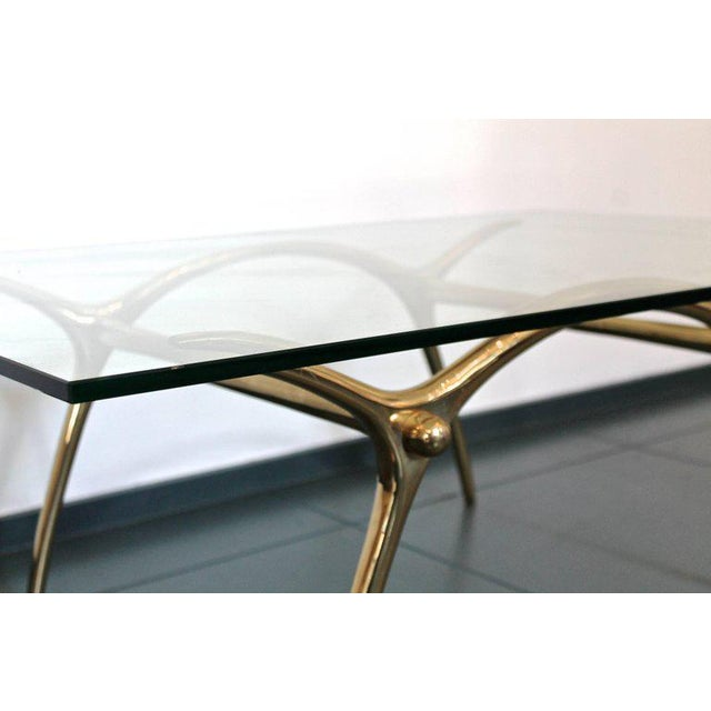 1970s coffee table in glass an brass by Belgian designer Kouloufi. A rectangular shaped cocktail table featuring a...