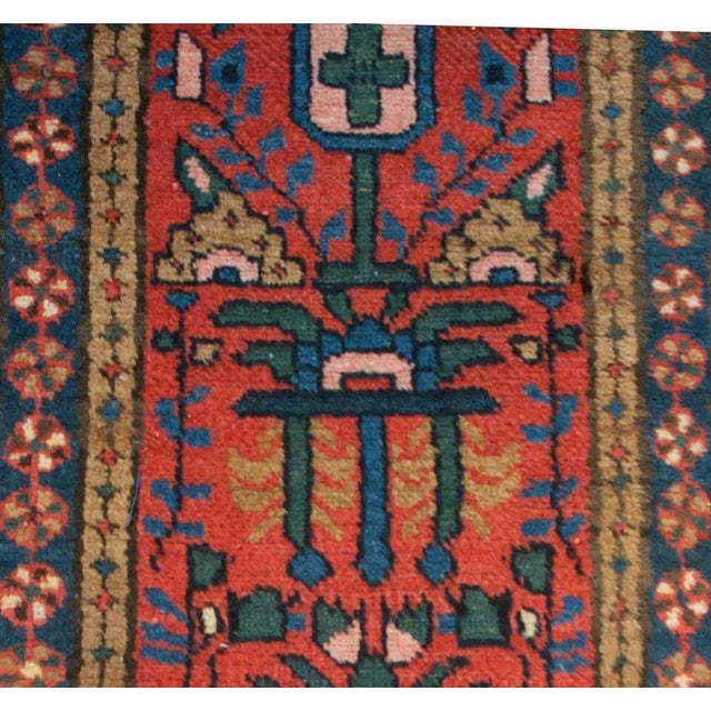 An early 20th century Persian Heriz runner with a bold indigo, emerald and taupe floral pattern on a crimson background,...