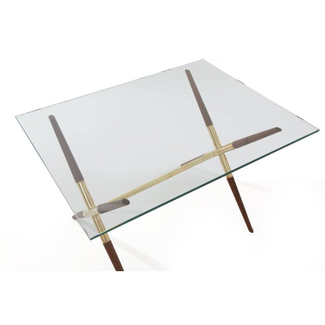Tapered solid walnut and polished brass cocktail or occasional table from Italy, circa late 1950s. This lovely example has...