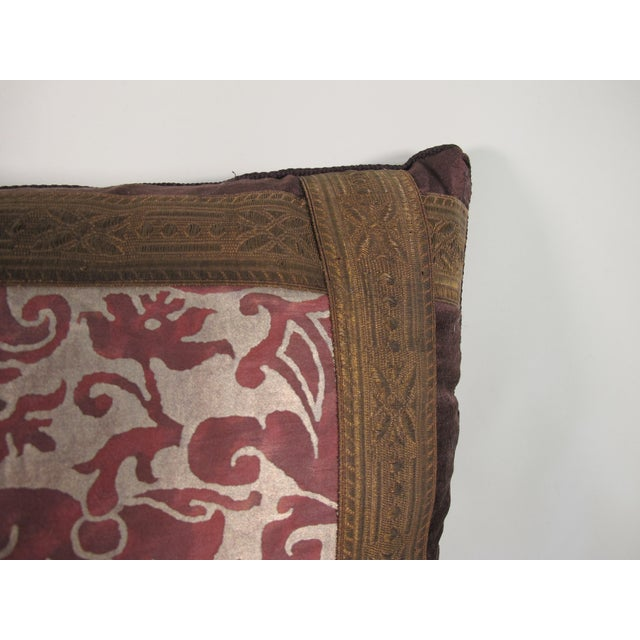A pillow made from a Fortuny fabric in the iconic Caravaggio pattern, embellished with antique metallic trim and backed...