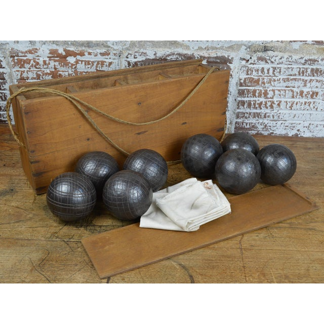 Late 19th century antique French boules set in wooden case. Set of 8 heavy cast iron balls have two different patterns and...