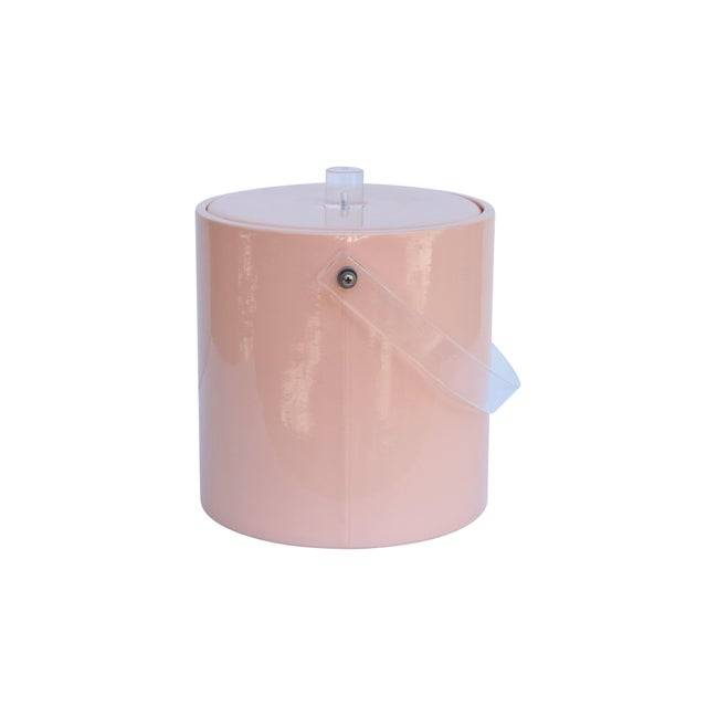 A mid century ice bucket in blush. The lid is padded with a cylindrical lucite knob handle at the center. The bucket has a...