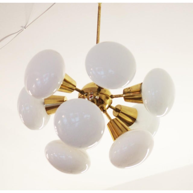 This space age chandelier originates from the 1960s. It is made of polished brass with nine round white opalescent glass...