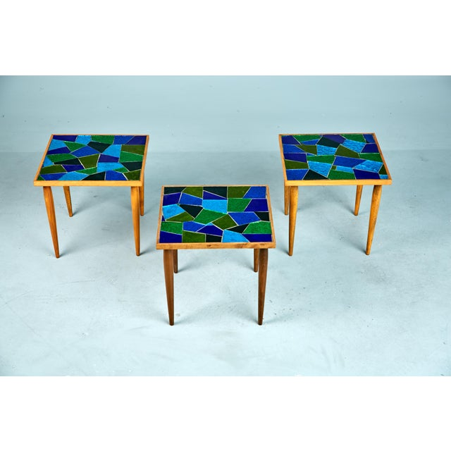 Set of three (3) walnut side or accent tables with slender conical legs. The tops are comprised of light reflecting inset...