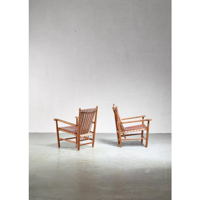 A pair of mid-century armchairs by Albert Haberer for Hermann Fleiner. The chairs are made of cherry wood and have a...