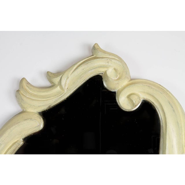 A stunning Regency Moderne asymmetrical cartouche-form wall mirror with a molded plaster frame.