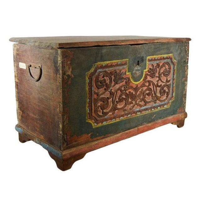 A 19th century hand-carved and painted Indonesian trunk with foliage motifs. This rectangular trunk rests on four small...