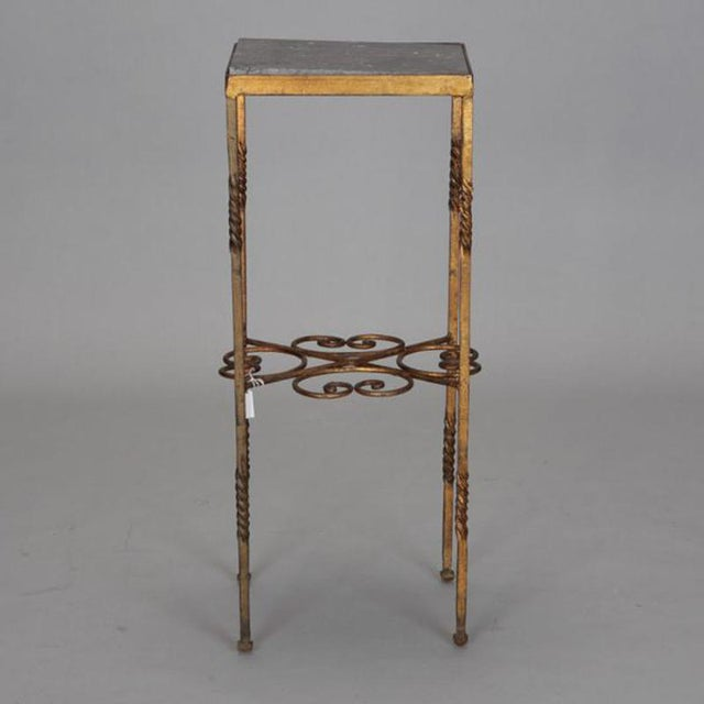 Circa 1920s Italian statue stand has gilded wrought iron frame with dark marble table top. Unknown maker.
