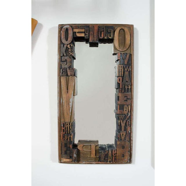 A graphic three-dimensional framed mirror comprising letters in various sized woodcuts on a sturdy wood and cement back....