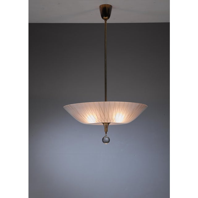 A very rare, custom-made pendant lamp by Lisa Johansson-Pape. The lamp has a curved frosted glass shade with a hand-...