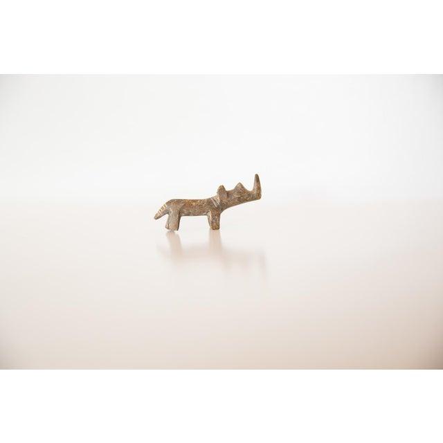 :: Vintage handmade bronze sculpture of a miniature rhinoceros with a light greenish tint to it. Circa mid 20th century...