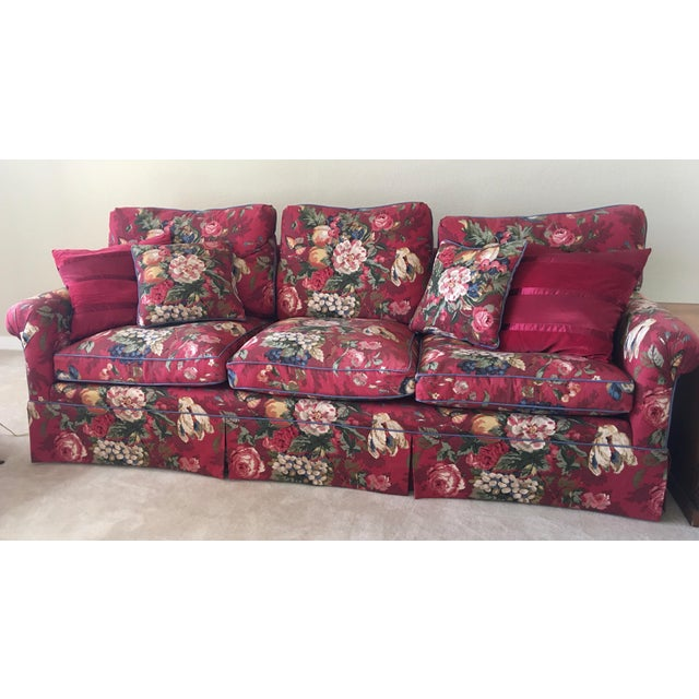 This sofa was recovered circa 2000 from its original fabric in this bright, cheery, floral, fruit design with a cornflower...