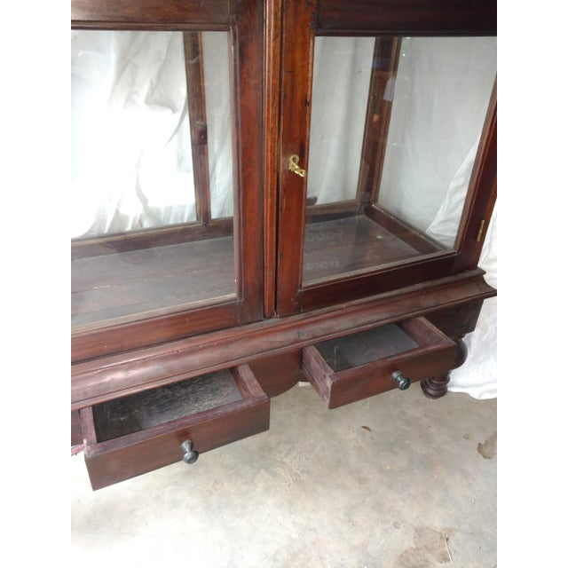 1930s Rosewood plantation display cabinet. Unique with two cabinet doors and glass on each side as well as both ends. It...