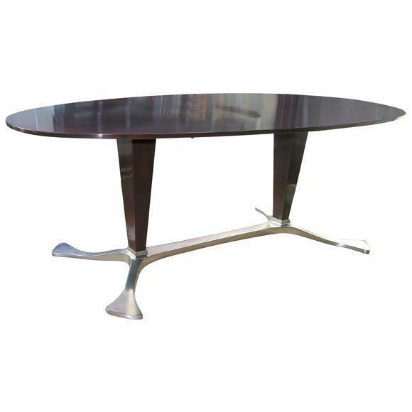 Amazing dining table by osvaldo borsani, all rosewood in a stunning wine color on a cast aluminum base. The use of...