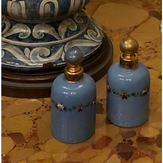 A pair of antique perfume bottles. Blue with gold tops and hand painted florals. Circa 1900.