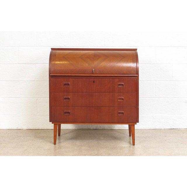 This iconic mid century Swedish modern Egon Ostergaard teak cylinder rolltop secretary desk cabinet is circa 1970. The...