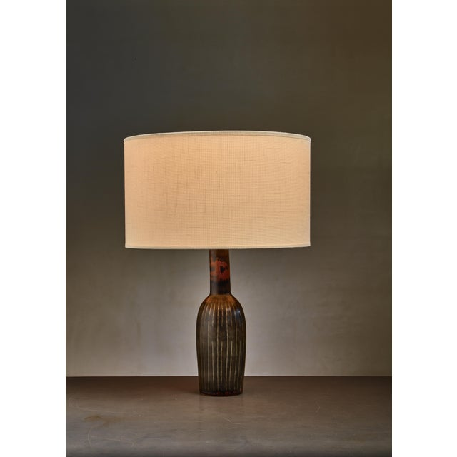 A dark green and brown ceramic table lamp by Carl-Harry Stålhane for Rörstrand. Marked by Stålhane and Rörstrand. The...