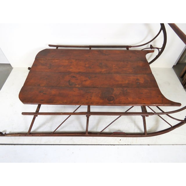 Offered is a large primitive style sled. Features iron and pine planks.