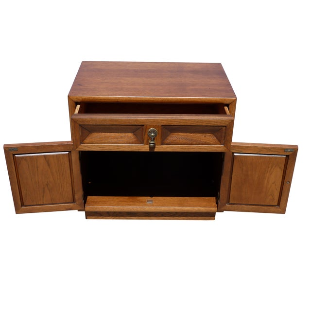 Slightly gothic and very substantial, these nightstands are made of walnut with brass hardware and feature a drawer and 2...