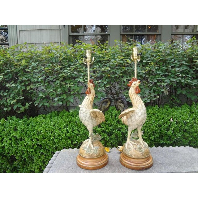 Lovely pair of French polychromed cast iron rooster lamps. These French lamps are executed in a beautiful soft palette...