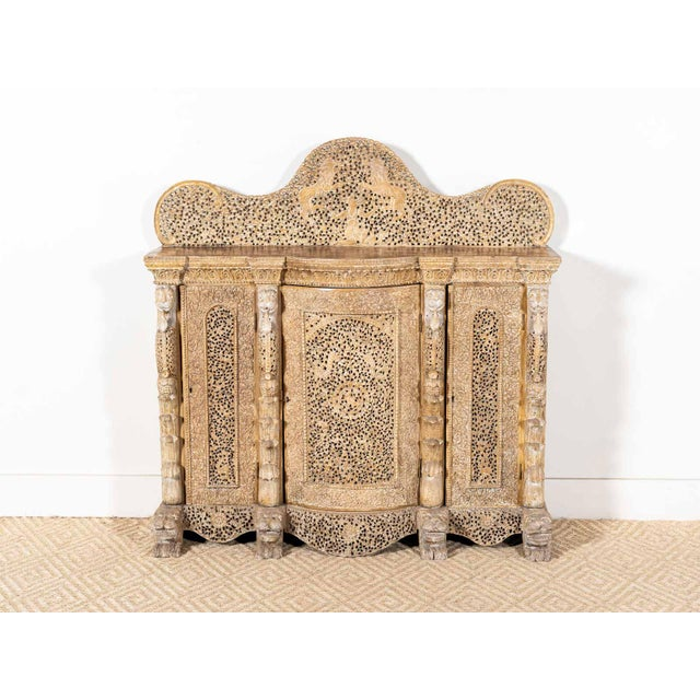 Light wooden sideboard with heavily carved fretwork Pierced flowering vines with lion motifs and feet Three rounded doors...