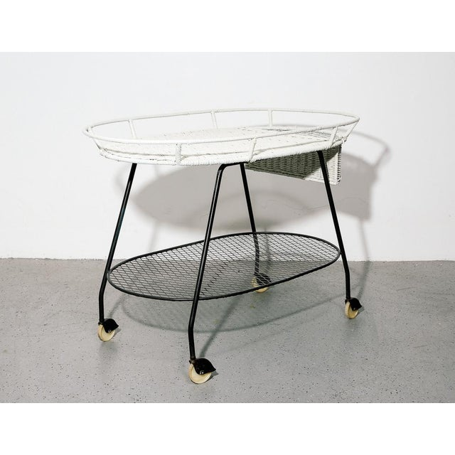 Vintage bar cart by Salterini. White painted wicker top and basket over black steel frame. On casters.