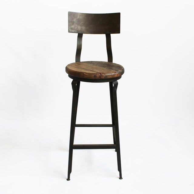 Old wood round seat bar stool with industrial iron legs and back rest. This bar stool has an industrial look perfect for...