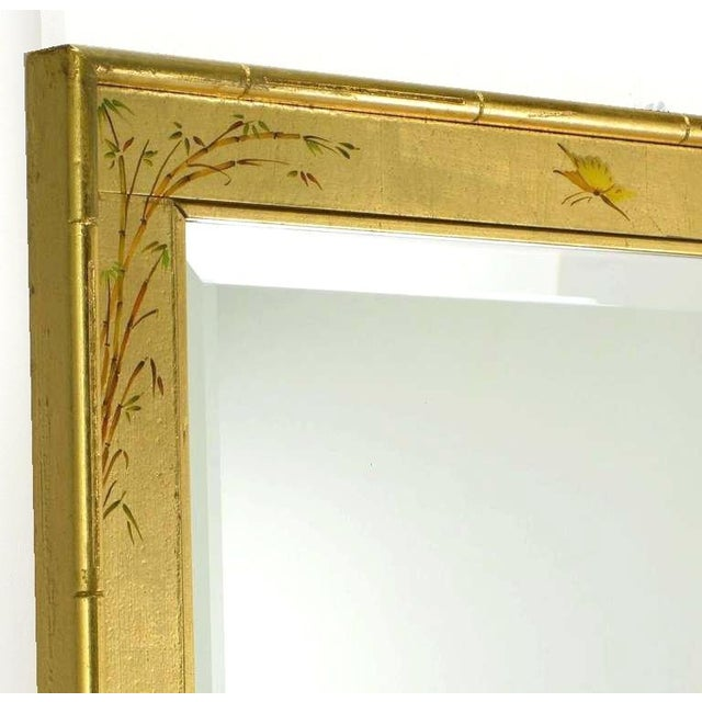 LaBarge gilt and hand painted wall mirror. Gilt finish with amber lacquer and hand painted with Asian flora and fauna....