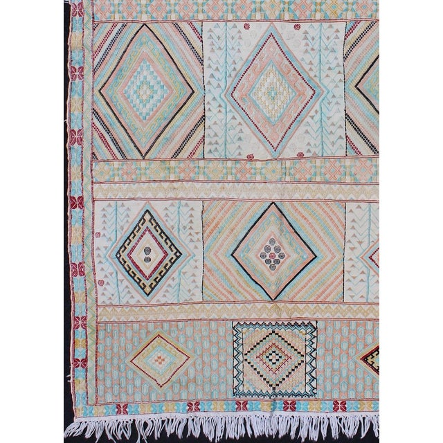 This brilliant Moroccan kilim rug displays multicolored diamond shapes in a box-style design across the field. The...