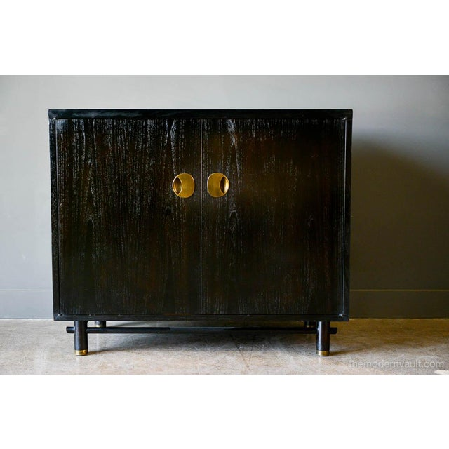 Ebonized cabinet with brass hardware by Baker, circa 1970. Brass hardware on door and legs. Two inner drawers with a...