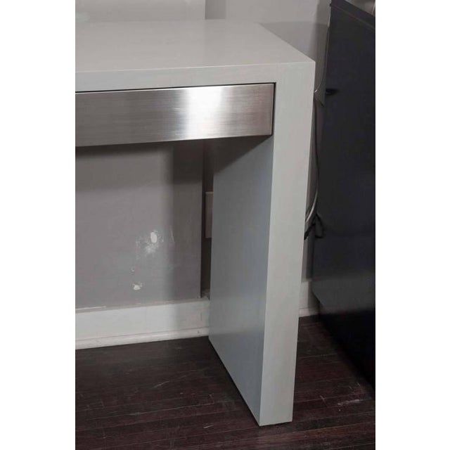 Custom gray stained console with brushed stainless steel drawers.