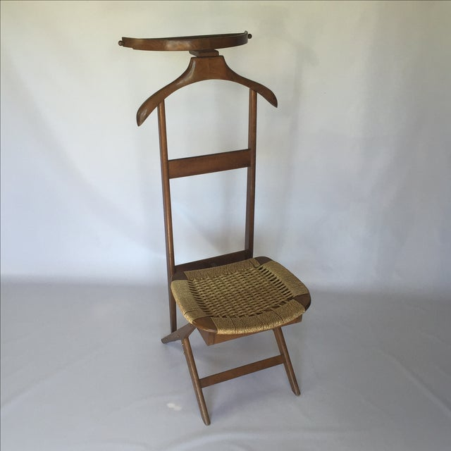 This vintage Danish style valet is in excellent condition. Seat opens for additional storage.