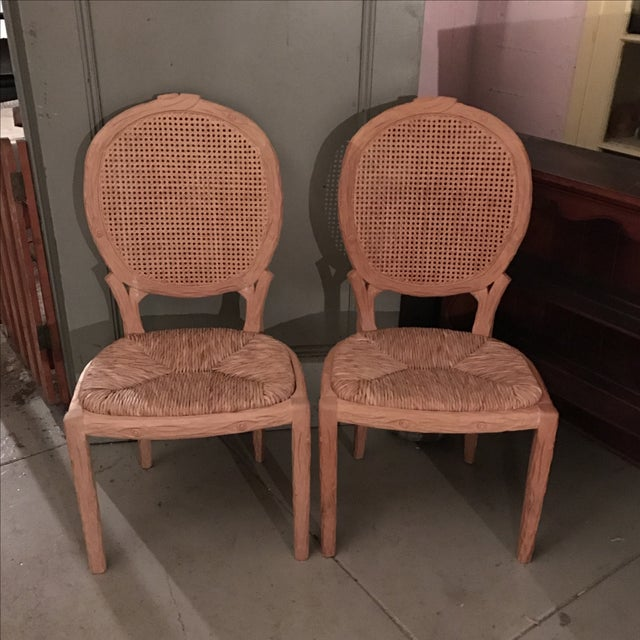Pair of unfinished carved wooden frames with cane backs and rush slip seats .